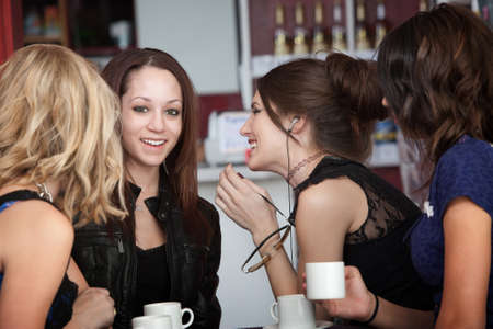 Four young women sharing secrets at a cafe Stock Photo