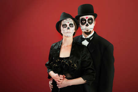Classic vintage woman poses with black roses and her husband in makeup for All Souls Day photo