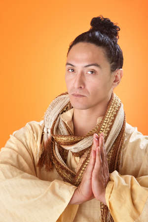 Man makes a traditional Asian greeting in robe and scarf photo