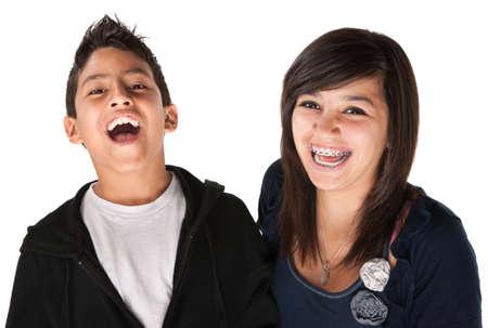 orthodontics: Dos ni�os hispanos riendo sobre fondo blanco Foto de archivo