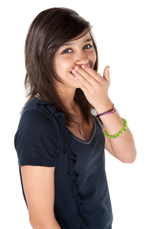 Cute Hispanic teenage girl covering her braces with hands and a big smile photo