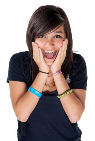 ortodoncia: Ni�a latina sorprendi� y manos en la barbilla con gran sonrisa sobre fondo blanco Foto de archivo