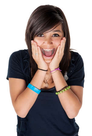 orthodontics: Young latina girl surprised and hands on chin with big smile on white background