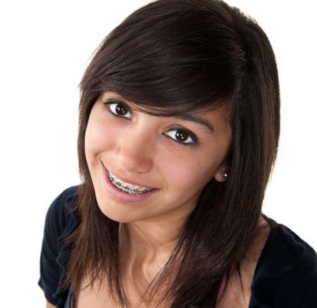 orthodontics: Linda chica adolescente Latina sonriendo con llaves sobre un fondo blanco