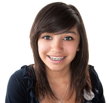 cute braces: Cute Hispanic teenage girl smiling with braces on a white background Stock Photo