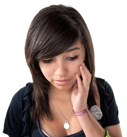 Sad Hispanic girl with hand on chin on white background photo