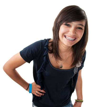 Cute hispanic teenage girl with braces and a big smile while hand on hip