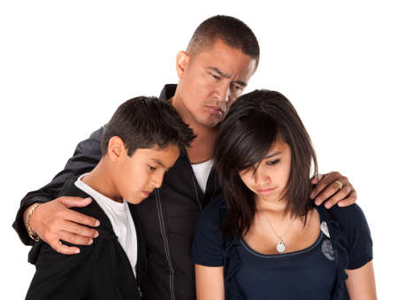 children sad: Hispanic father with kids looking down and sad on white background Stock Photo