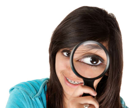 Young girl looking through a magnifying glass photo