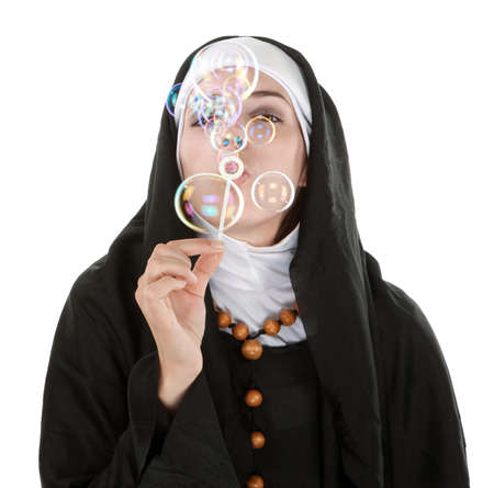 Young nun on white background blowing bubbles photo