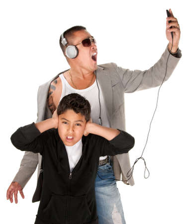 Hispanic youngster covers ears while father sings to music from an mp3 player photo