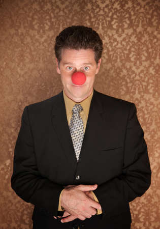Young businessman with folded clasped hands and clown nose photo