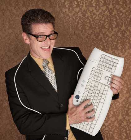 Caucasian business man playing guitar with a computer keyboard