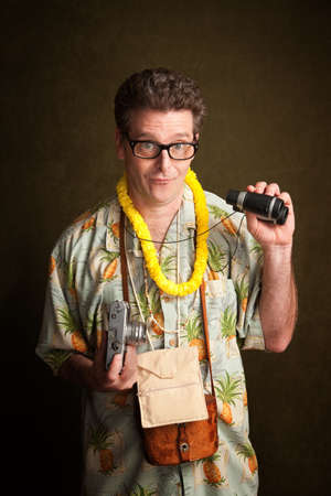 Male tourist in a tropical island outfit holding a camera and binoculars Stock Photo - 8925068