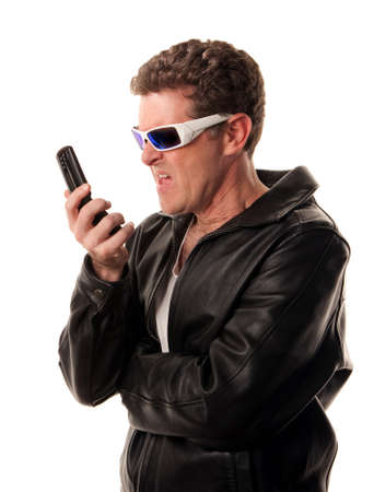 Man in leather jacket looks at his cell phone in disgust photo
