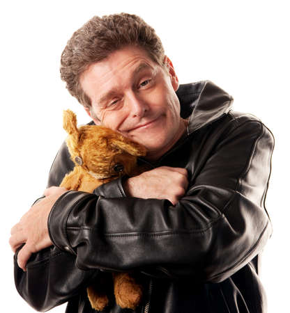 strong: Caucasian man in leather jacket hugs a brown bear