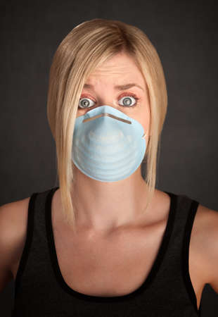 Worried young blonde woman with surgical mask on a grey background photo