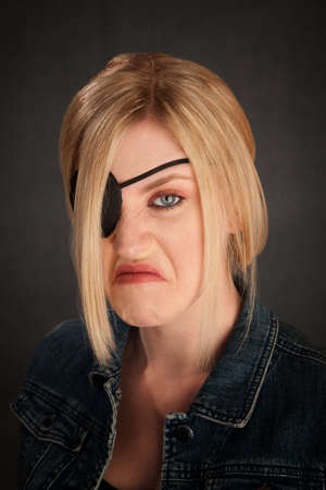Angry blonde girl with eyepatch on grey background photo