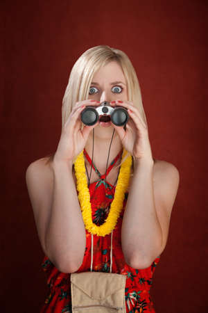 Shocked woman tourist with garland looking through binoculars Stock fotó