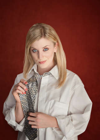 Pretty young blonde woman in boyfriends shirt and holding tie with hands on red background photo
