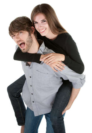 Young handsome man carries a cute lady on his back