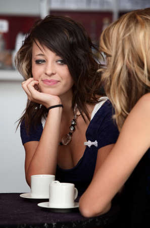 Cute teenage girl listening to her friend in a Cafe photo