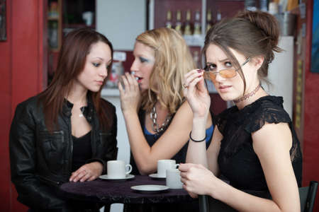Two friends share a secret while a woman looks away with eyeglasses down