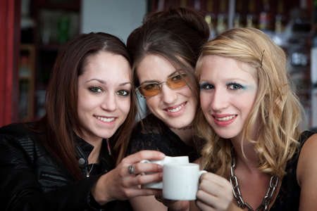 sorority: Three cute teenaged friends smiling and saying cheers over coffee