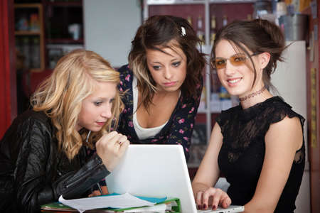Three cute teenaged girls share a laptop while doing homework in a cafe photo