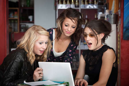 Three young female students surprised while looking at a computer