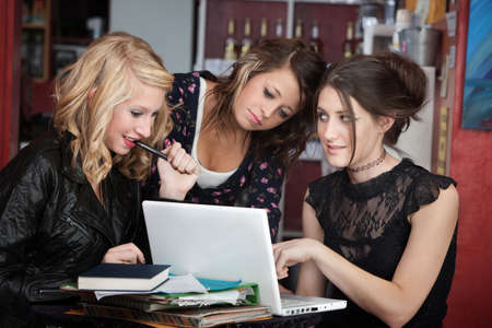 clarify: Cute teenaged girls distracted with a laptop while doing homework in a cafe