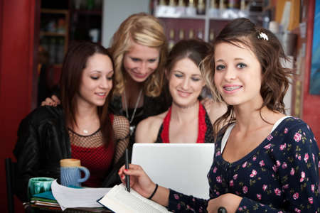 test deadline: Cute teenaged girl does homework with friends in a cafe