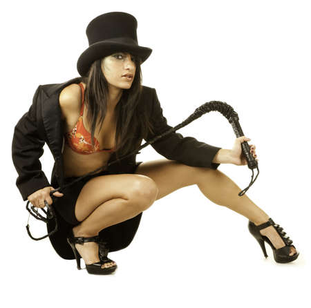 Sexy female lion tamer in circus top hat crouching photo