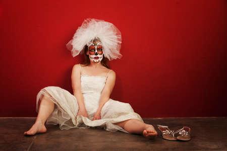 Sexy bruid in make-up voor alle zielen dag zit op de grond