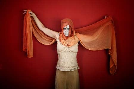 빨간색 배경에 그녀의 팔을 확산 스카프와 모든 영혼의 날에 대 한 메이크업에 여자
