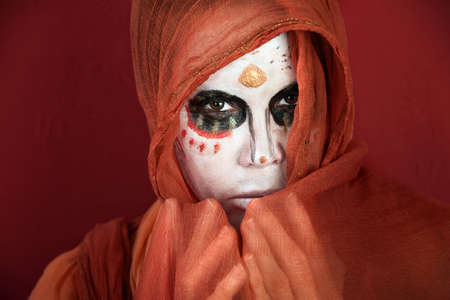 Woman in makeup for Day of the Dead with a scarf around her face photo