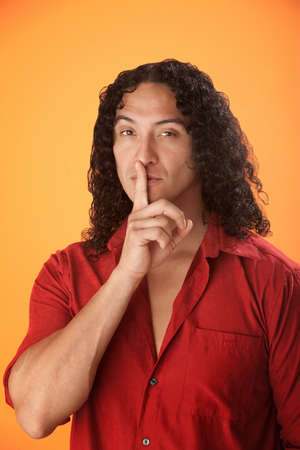 Well built Hispanic man with finger to his lips photo