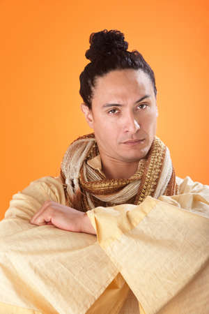 eyebrow raised: A serious looking japanese samurai on orange background with folded hands Stock Photo