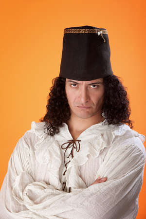 beardless: Middle aged latino man looking stubborn in a traditional dress on orange background Stock Photo