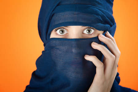 Young girl with a scarf covering her head and face photo