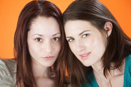 Two pretty young female friends together on a orange background photo