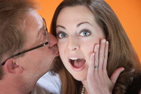 Man surprises young woman with a kiss on the cheek photo