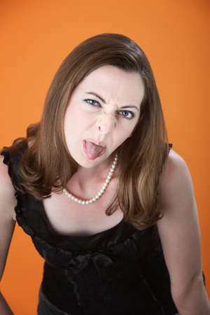 spit: Bratty Caucasian woman sticks her tongue out Stock Photo