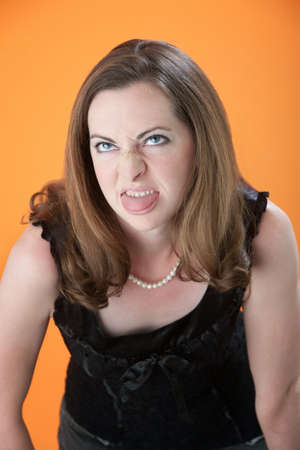bad manners: Disgusted female  on orange background biting her tongue