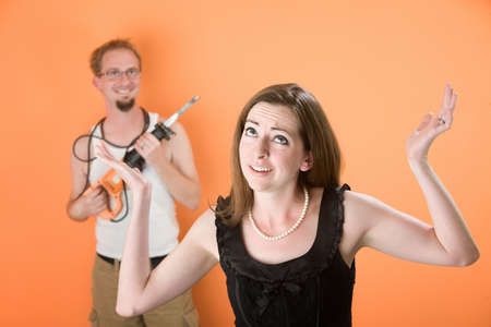 Frustrated young woman and handy husband with reciprocal saw photo