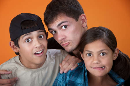a big family: Elder brother with two younger siblings making faces Stock Photo
