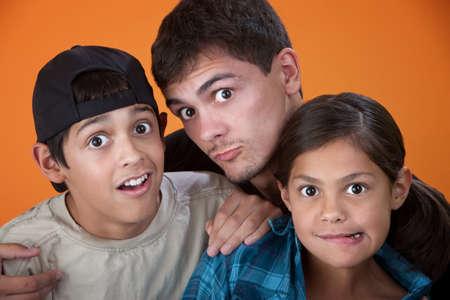 making faces: Fratello maggiore con due fratelli pi� giovani facendo facce