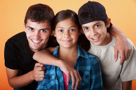 family unit: Caring brothers with their sister smiling on orange background