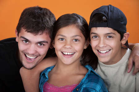 babysitter: Two caring brothers with sister smiling on orange background  Stock Photo