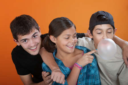 Young girl touching bubble from her brothers chewing gum on orange background